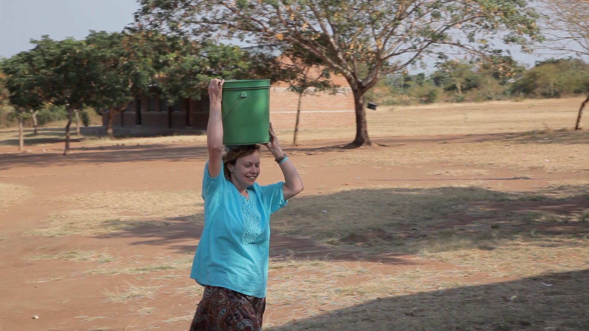 Susan carrying water on her head