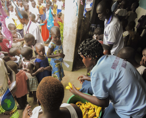 Community Health Worker Lilian Kayuni handing out bananas to the children after they washed their hands.